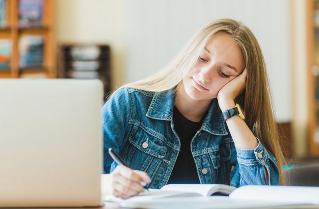adolescente-encantador-haciendo-notas-cerca-de-la-computadora-portatil_23-2147846729.jpg