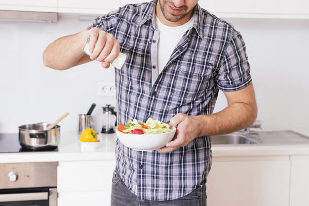 primer-plano-hombre-joven-que-agrega-sal-ensalada-verduras-mientras-cocina-cocina_23-2148120516.jpg