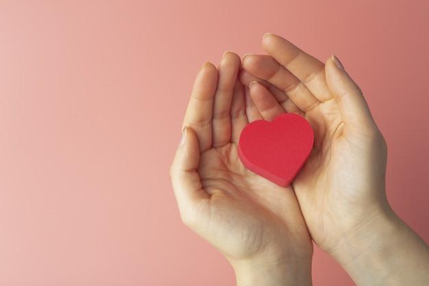 corazon-manos-mujer-sobre-fondo-color-fondo-san-valentin-14-febrero-amor_90380-2172.jpg