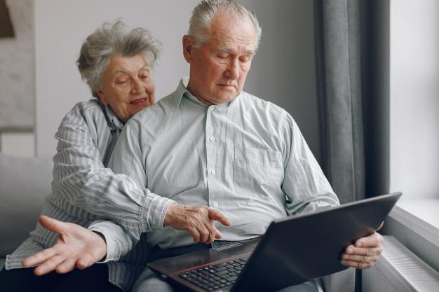 elegante-pareja-ancianos-sentados-casa-usando-computadora-portatil_1157-31934.jpg