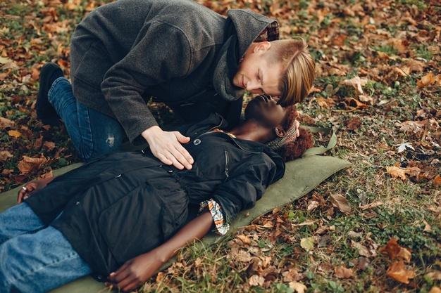 guy-ayuda-mujer-chica-afro-inconsciente-proporcionar-primeros-auxilios-parque_1157-40365.jpg