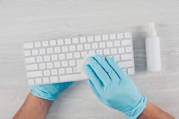 hombre-guantes-desinfectando-teclado-fondo-madera-clara-desinfectante_176474-2791.jpg