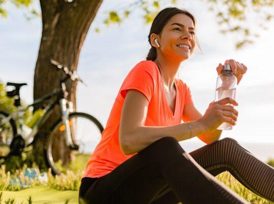 sonriente-mujer-hermosa-bebiendo-agua-botella-haciendo-deporte-manana-parque_285396-4388-e1611246858655.jpg